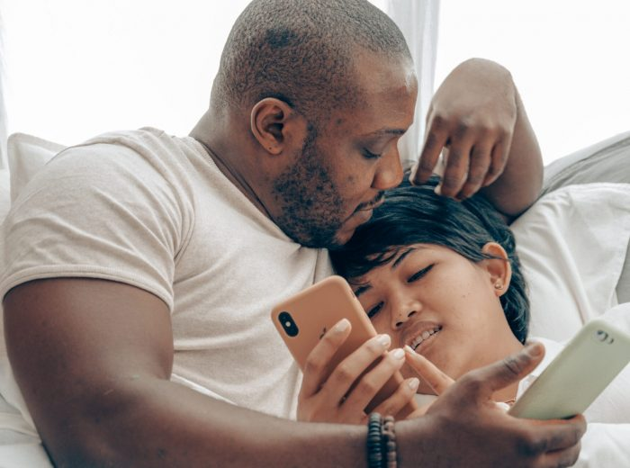 loving-diverse-couple-with-smartphones-in-comfortable-bed-4545206